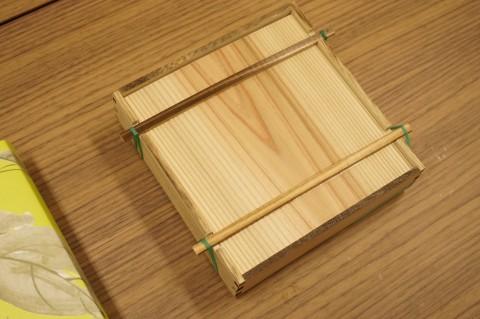 木桶のような箱。ふたは輪ゴムで留められている。